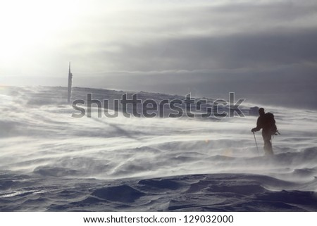 Mountaineer climbing the snowy mountain in stormy winds, Romania - stock photo