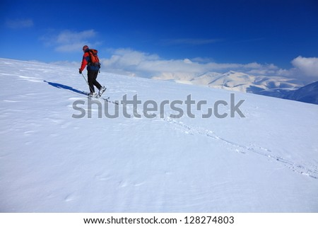 Mountaineer climbing the snowy mountain on ski during sunny winter day