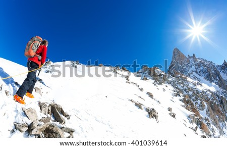 Mountaineer climbs a snowy peak. In background the famous peak Dent du Geant in the Mont Blanc Massif, the highest european mountain. The Alps, Chamonix, France, Europe.