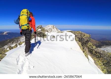 Mountaineer climbs sunny summit on packed snow - stock photo