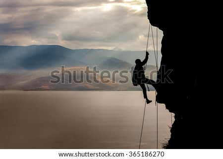 Mountaineer crawling on the mountain in the background Lake Baikal.