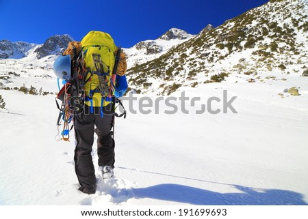 Mountaineer crossing a snow field in sunny day