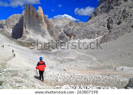 Mountaineer descending along winding path on large valley in Catinaccio massif, Dolomite Alps, Italy - stock photo