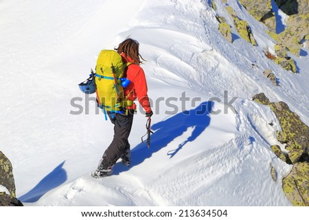 Mountaineer during winter climb on snow covered slope of a sunny mountain
