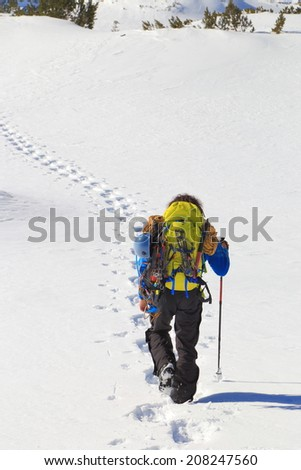 Mountaineer follows a trail of foot steps on the snow - stock photo