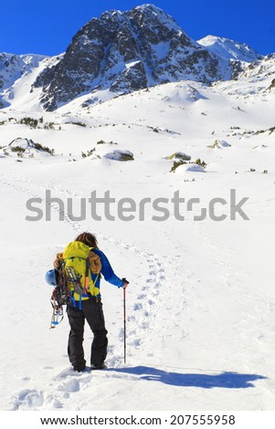 Mountaineer follows foot steps on a white snow field