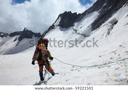 Mountaineer girl belaying friends by rope in mountains - stock photo