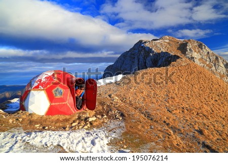 Mountaineer leaving the mountain refuge in the morning - stock photo