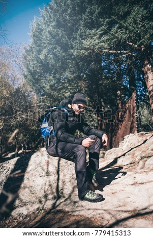 Mountaineer man with mobile phone hiking.