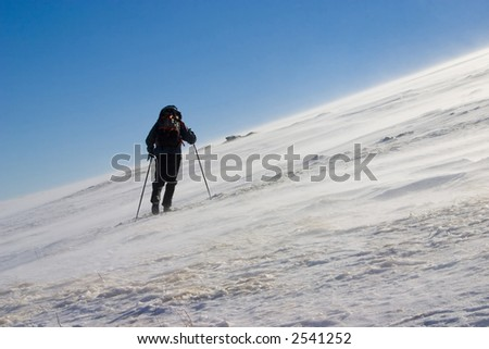 Mountaineer on a mountain slope, blowing wind