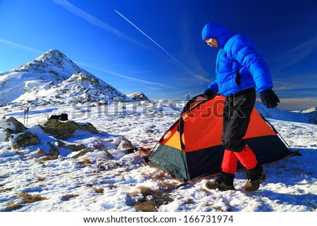 Mountaineer on snowy mountain pitching an orange tent