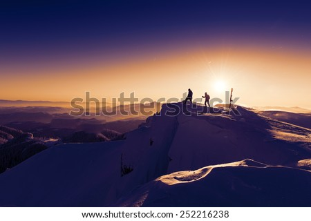 Mountaineer on snowy summit overlooking winter sunrise - stock photo