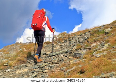 Mountaineer on sunny trail ascending a rocky slope under the blue sky - stock photo