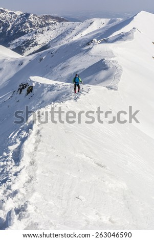 Mountaineer on the ridge in winter conditions