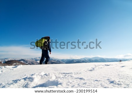 Mountaineer reaches the top of a snowy mountain. - stock photo