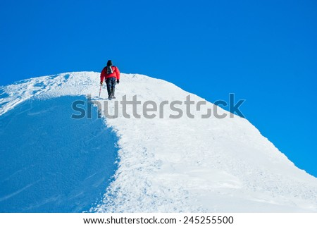 Mountaineer reaches the top of a snowy mountain - stock photo