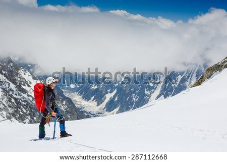 Mountaineer reaches the top of a snowy mountain in a sunny day - stock photo
