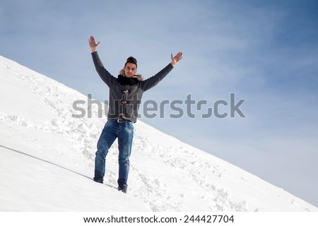 Mountaineer reaches the top of a snowy mountain in a sunny winter day. - stock photo