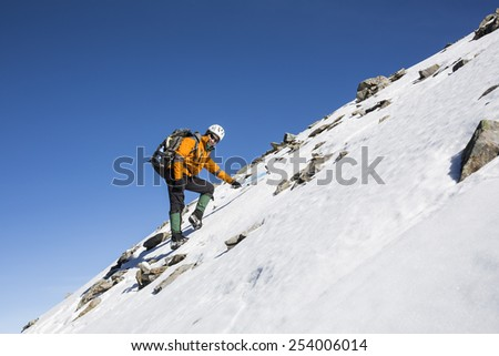 Mountaineer reaches the top of a snowy mountain in a sunny winter day