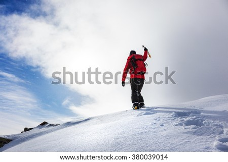 Mountaineer reaching the summit of a snowy peak in winter season. Concepts: determination, courage, effort, self-realization.