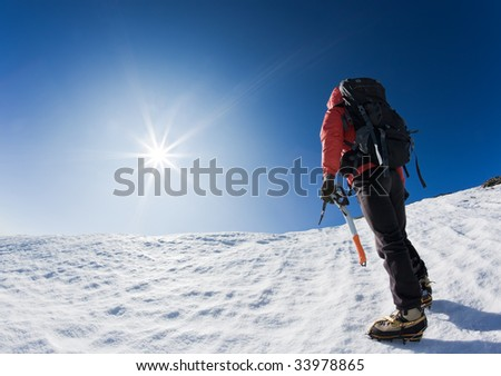 Mountaineer reaching the top of a snowcapped mountain peak. Horizontal frame.
