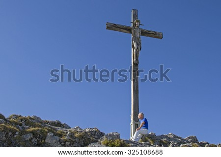Mountaineer reaching the top of the Kofel in the Ammergau Alps