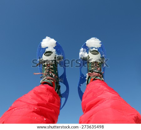 Mountaineer's legs with snowshoes for excursions on the snow in the mountains - stock photo