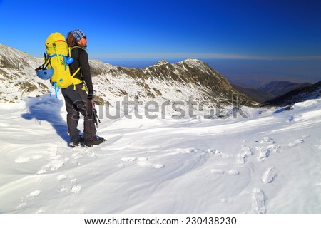Mountaineer sanding on a snow field in winter - stock photo
