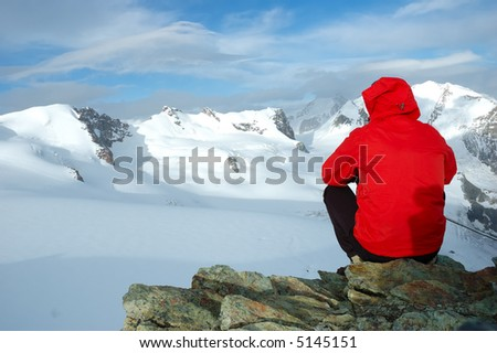 Mountaineer sitting on a stone looking at big glacier a snowed mountain. West Alps, Italy.
