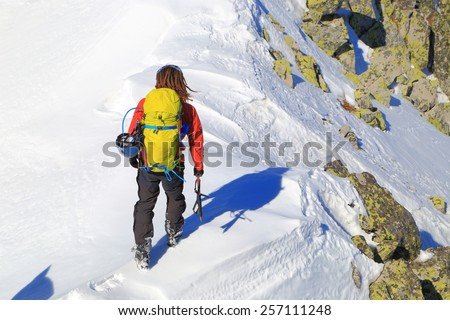 Mountaineer stepping on snow covered ridge in winter - stock photo