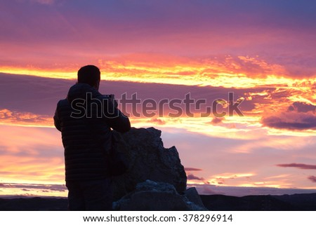 Mountaineer taking a photo of a sunset