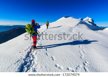 Mountaineer taking a photograph with a mobile phone on the Ko�¡uta ridge in Karavanke range in winter, Slovenia - stock photo
