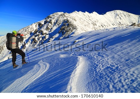 Mountaineer taking pictures of the snowy mountains