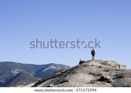 Mountaineer walking in the mountain and the moon