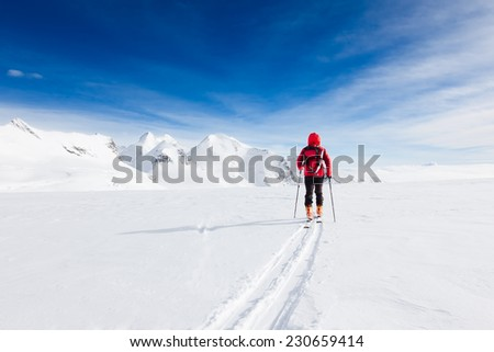 Mountaineer walking on a glacier during a high-altitude winter expedition in the european Alps. Breithorn, Monte Rosa massif, Valle d'Aosta, Italy, Europe. - stock photo