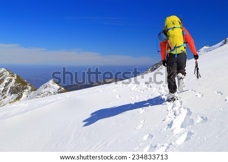 Mountaineer walking on a snow covered trail in sunny winter day