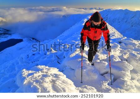 Mountaineer walking on sunny ridge at sunset - stock photo