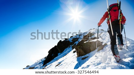 Mountaineer walking up along a snowy ridge with skis in the backpack. In background blue sky and shiny sun. Concepts: adventure, determination, extreme sport. Large copy-space on the left for text. - stock photo