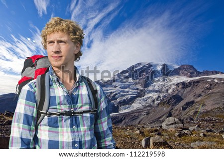 Mountaineer with a backpack keeping an eye out for weather changes - stock photo