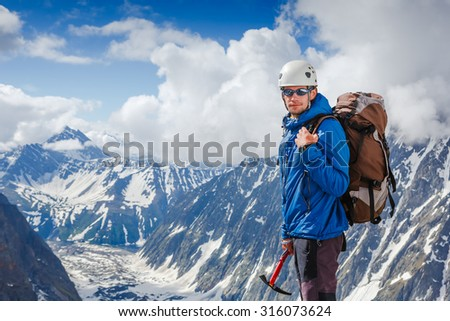 Mountaineer with ice ax reaches the top of a snowy mountain in a sunny winter day - stock photo