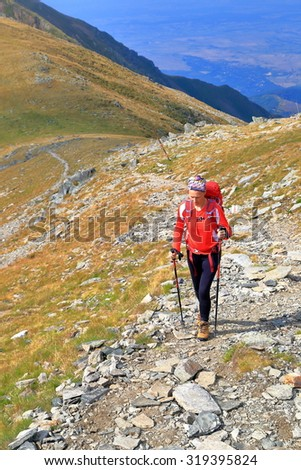 Mountaineer woman carries a backpack on a mountain trail  - stock photo