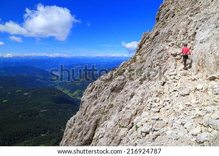"Mountaineer woman climbs on via ferrata ""Passo Santner"", Catinaccio massif, Dolomite Alps, Italy"