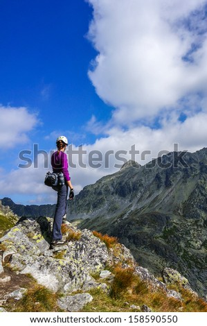 Mountaineer woman with helmet enjoying view in the mountains. High Tatra Mountains, Carpathians, Slovakia.