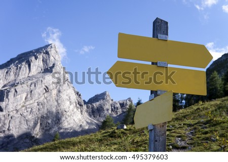 Mountaineering and hiking sign with directions and paths on a lush green meadow with a mountain peak in the background