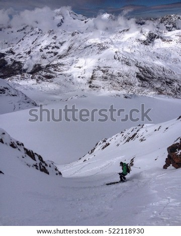 Mountaineering skier skiing down a snowy mountain in winter