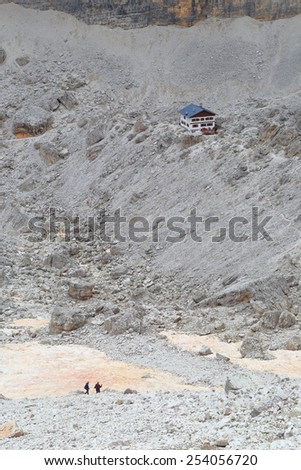 Mountaineers approaching Pomedes refuge on rocky valley, Tofana massif, Dolomite Alps, Italy - stock photo