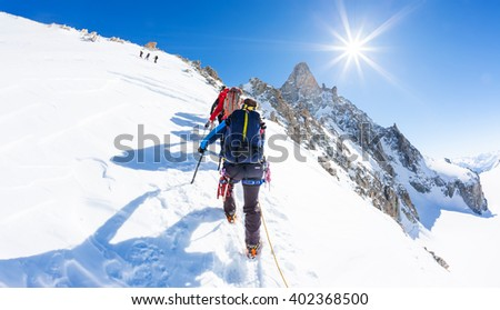 Mountaineers climb a snowy peak. In background the famous peak Dent du Geant in the Mont Blanc Massif, the highest european mountain. The Alps, Chamonix, France, Europe. - stock photo