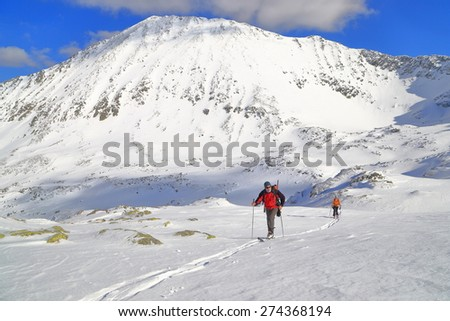 Mountaineers on touring skis traversing wide plateau in sunny winter day - stock photo