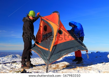 Mountaineers pitching an orange tent in winter - stock photo