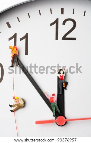 Mountaineers Scaling The Hands Of A Clock, macro of miniature models of mountaineers climbing the hands of a clock, time five minutes to twelve. - stock photo